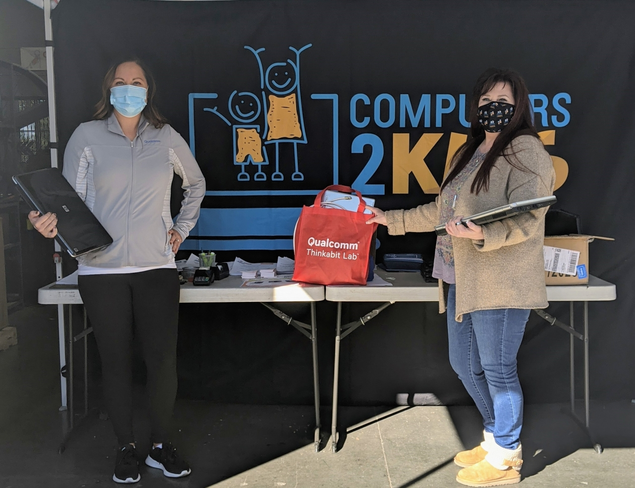 Natalie Dusi (L), Manager of Government Affairs, drops off a tech device donation to Cheri Pierre(R), CEO of Computers 2 Kids, as part of the drive which kicked off on National STEM Day 2020.