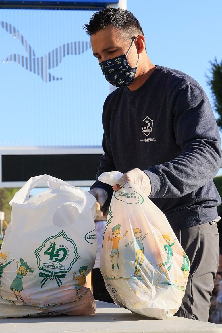 LA Galaxy volunteer distributes groceries to 350 vulnerable students during LA Harbor College's Spring Food Distribution event