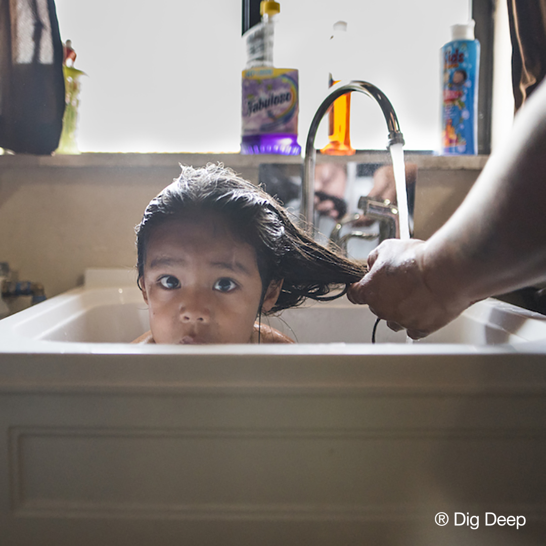 Child getting hair washed in sink