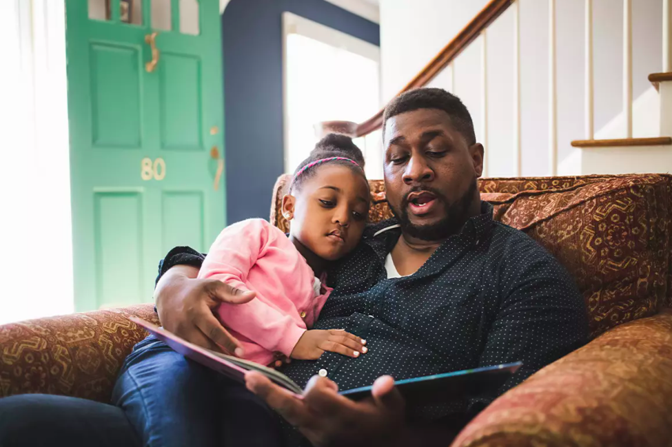 Father reading a book with daughter on couch