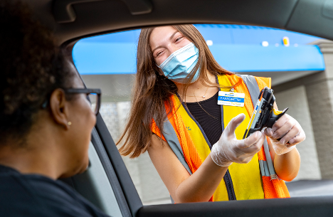 masked walmart employee interacting with a driver during a customer pickup