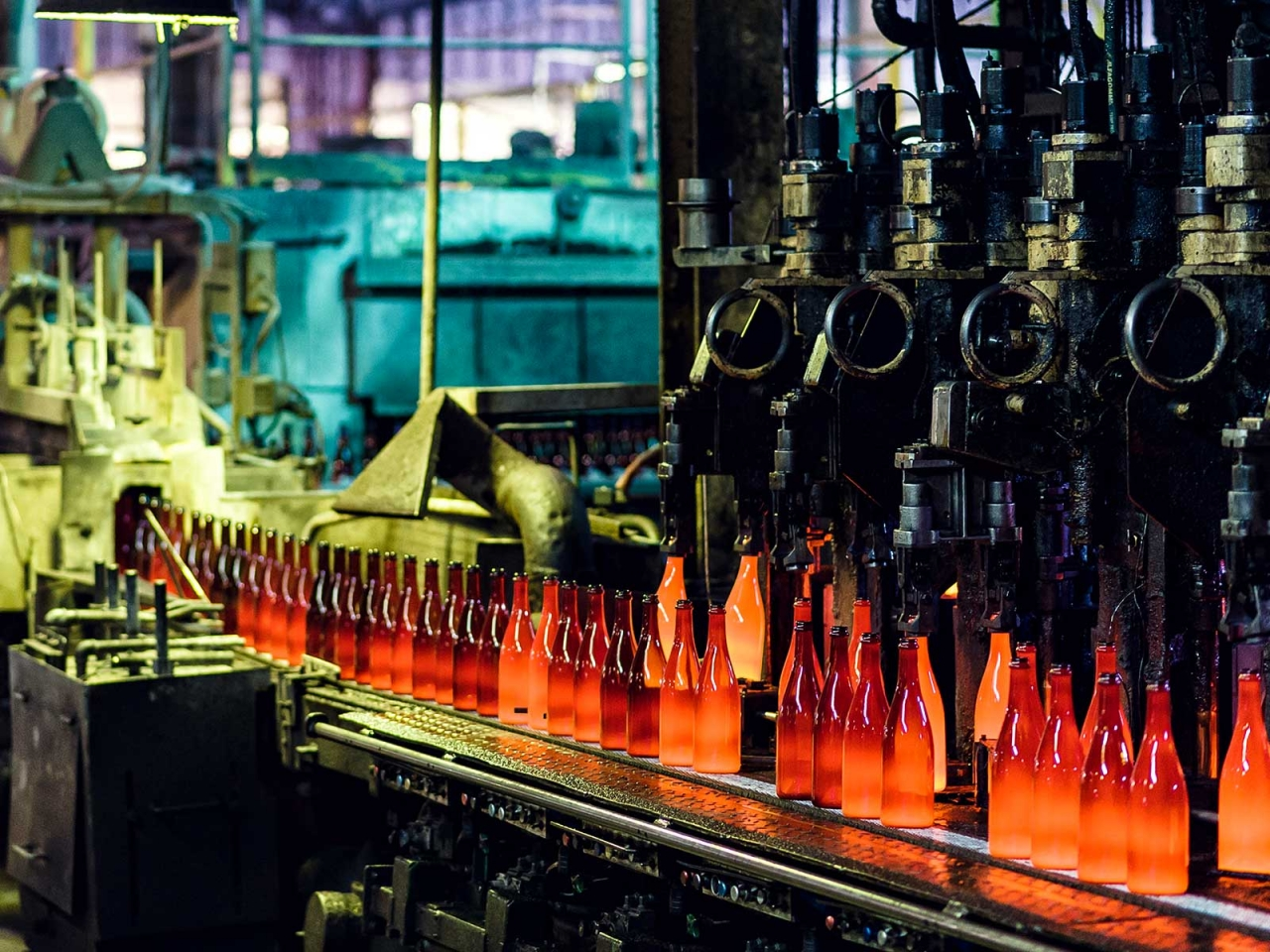 Bottling plant shown with a row of orange and red filled glass bottles