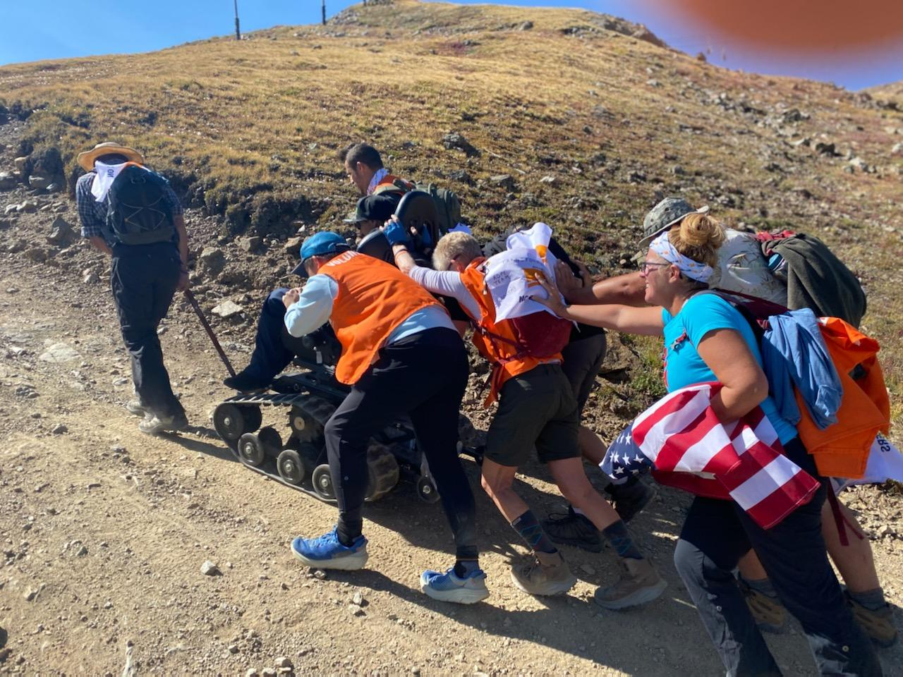 Hikers push a wheel chair up hill