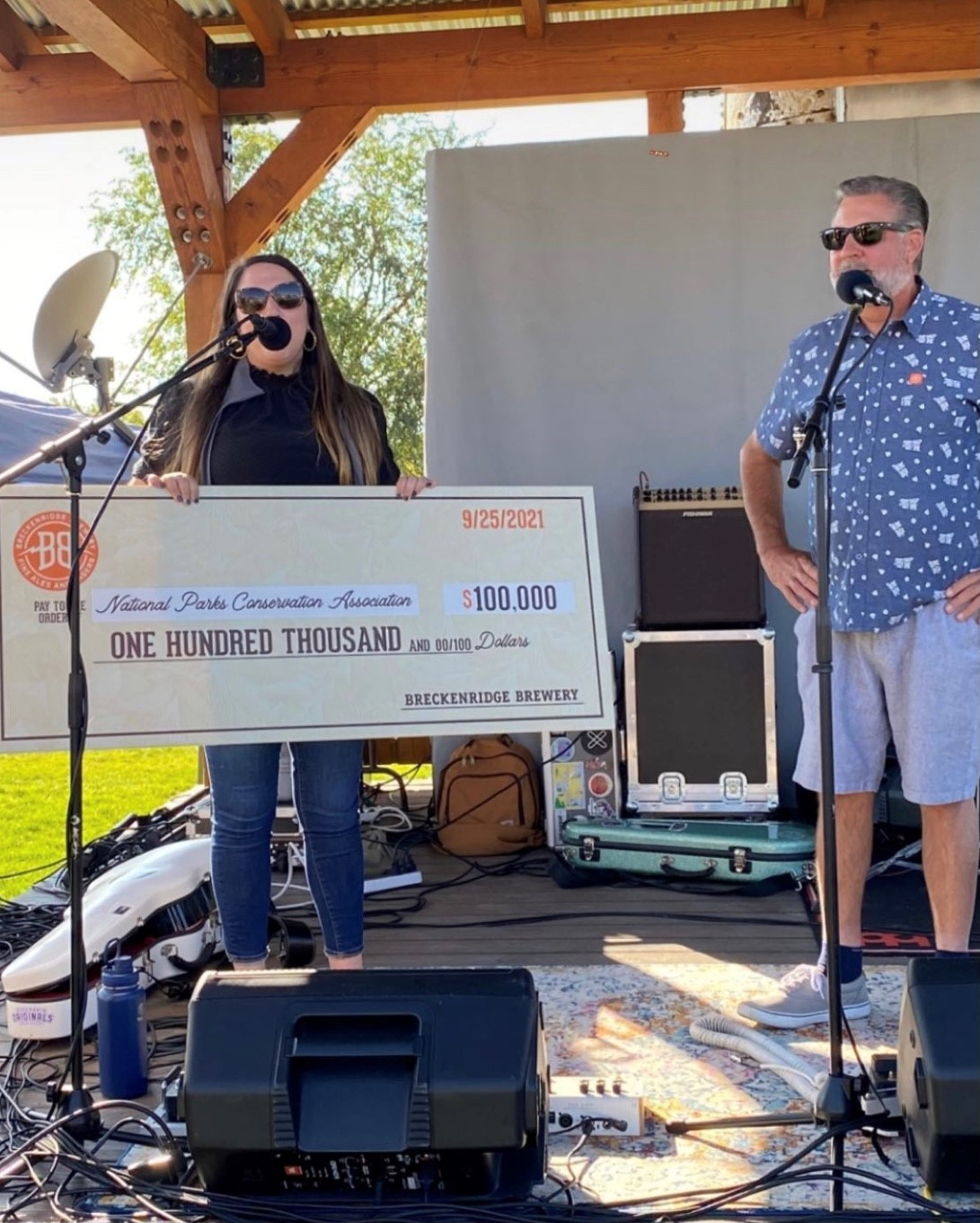 Breckenridge Brewery presents NPCA with a donation for $100,000. 2 people pictured in front of microphones with a big check for $100,000