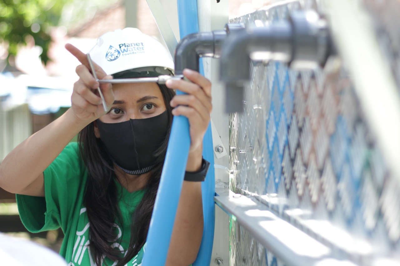 A Starbucks volunteer supporting the installation of an AquaTower in Indonesia