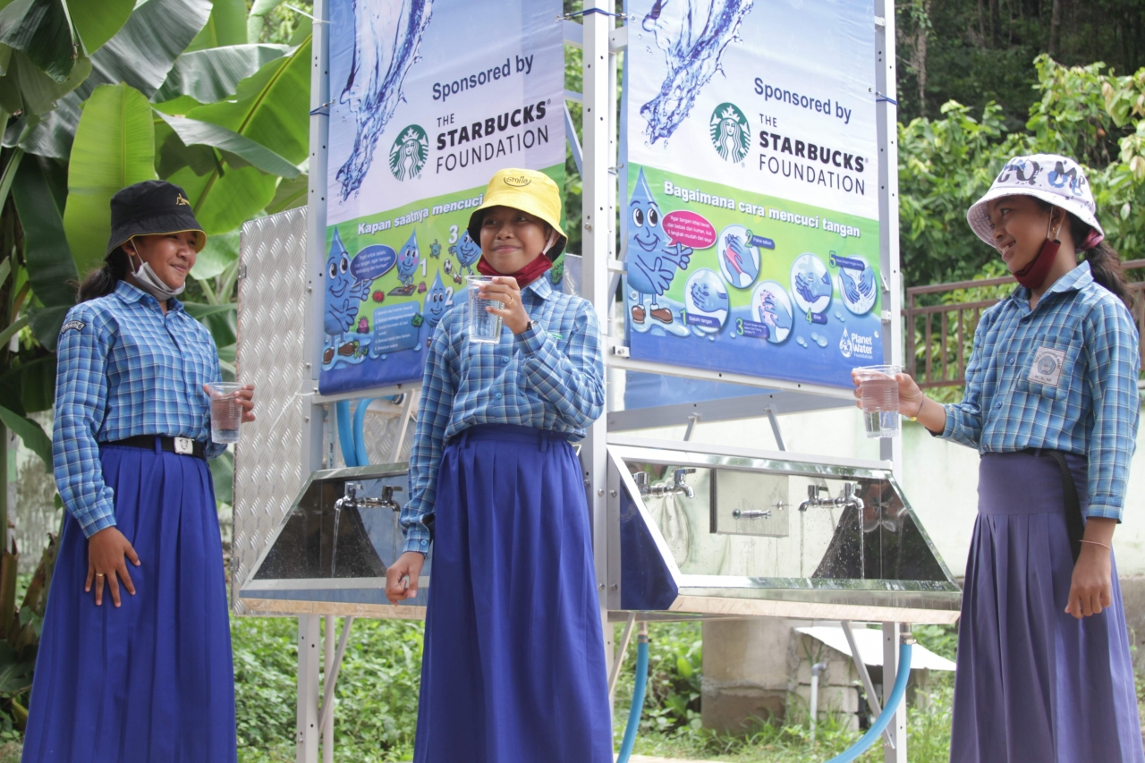 Children in Indonesia drinking water from an AquaTower supported by The Starbucks Foundation