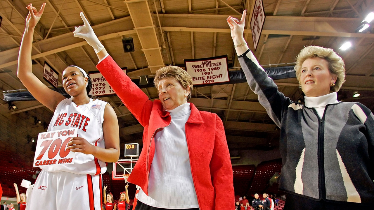 An NC state player and two coaches raise their hands making a symbol with their fingers