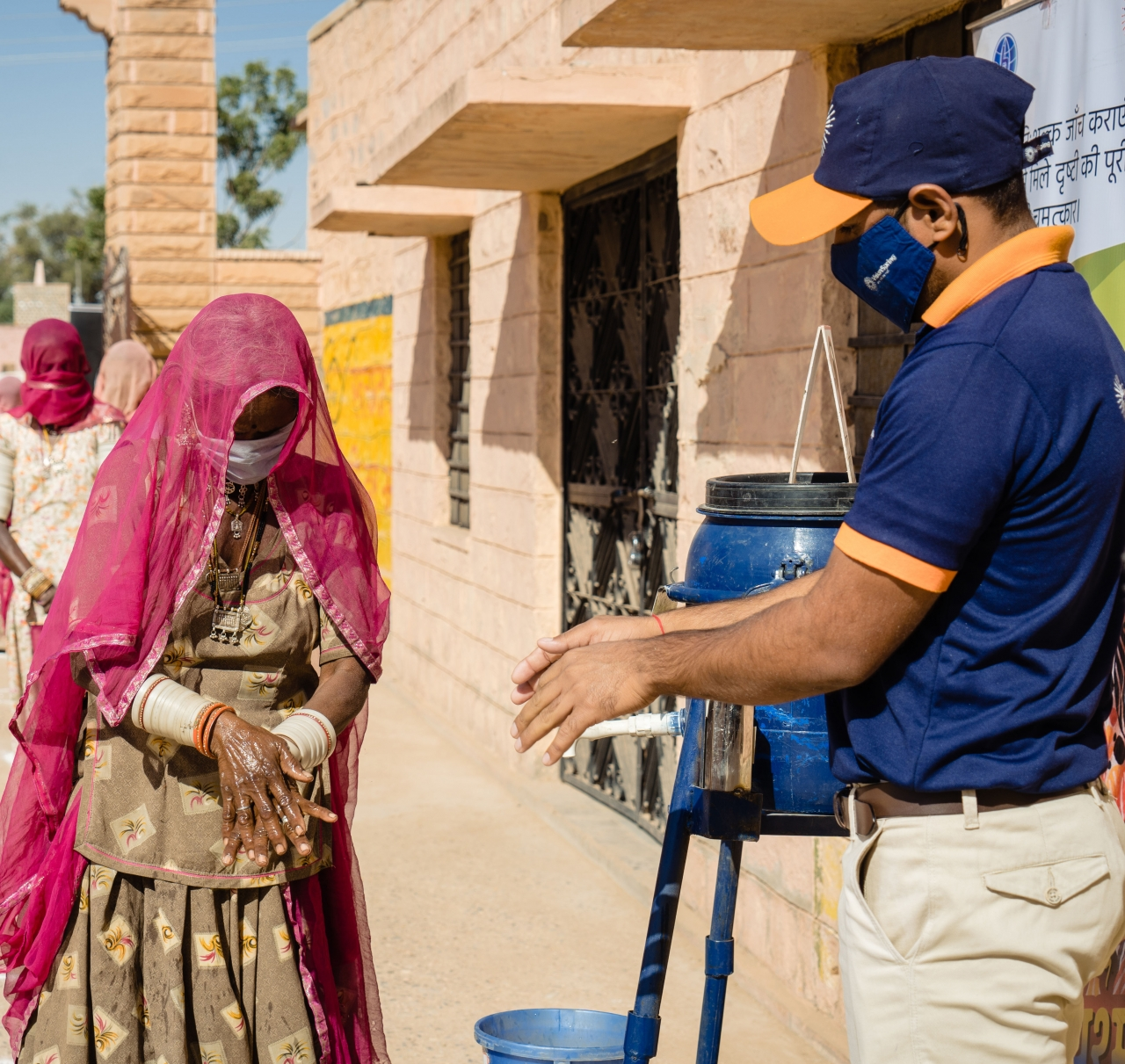 Dai Devi, a weaver in rural Barmer, Rajasthan, washing her hands at a handwashing station provided by VisionSpring. Hand hygiene to prevent the spread of COVID-19 is a core pillar of VisionSpring's emergency response.