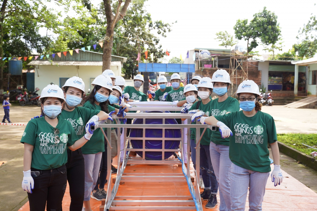 Starbucks volunteers assemble an AquaTower in Vietnam