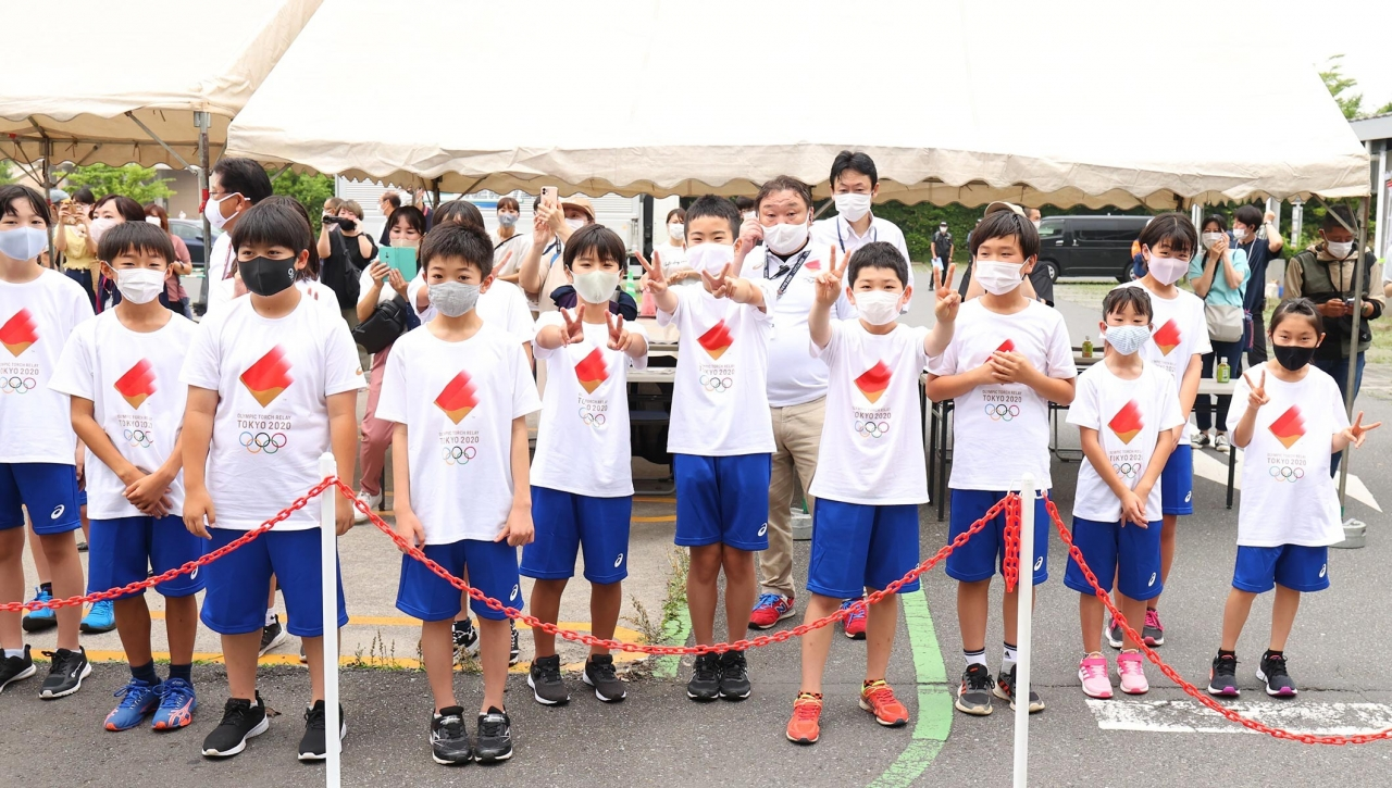 11 Japanese children stand waiting to enjoy the 2020 Tokyo Games