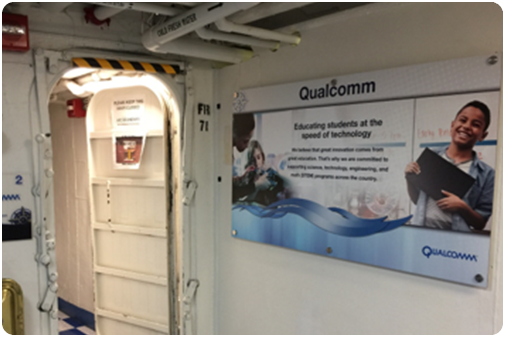 Qualcomm education poster hanging in hallway