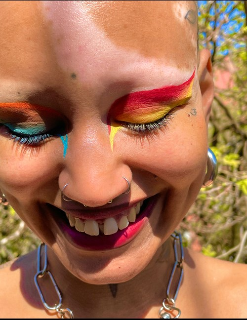 A person smiling with multiple piercings and colorful makeup