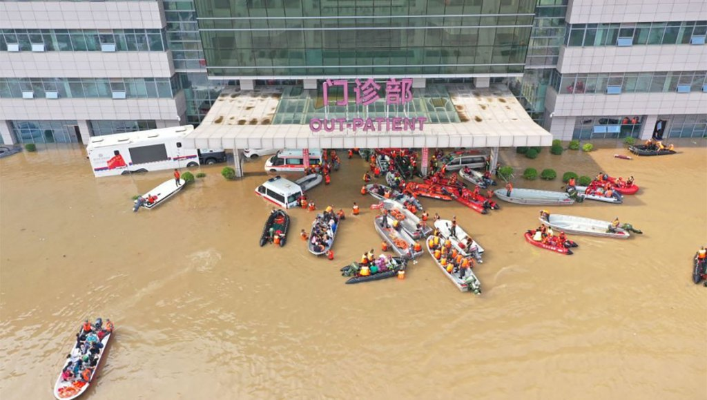 Image shows flooded hospital with many life boats escorting people to safety