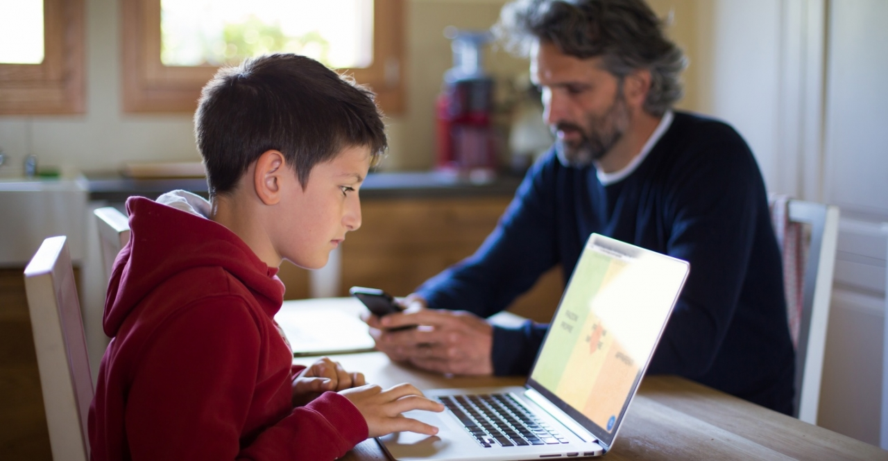Child on computer while dad uses smartphone