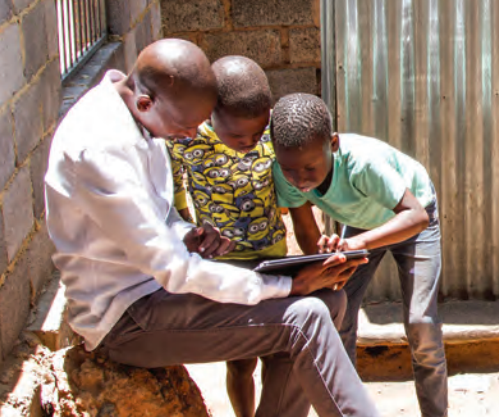 2 kids and a teacher use a tablet