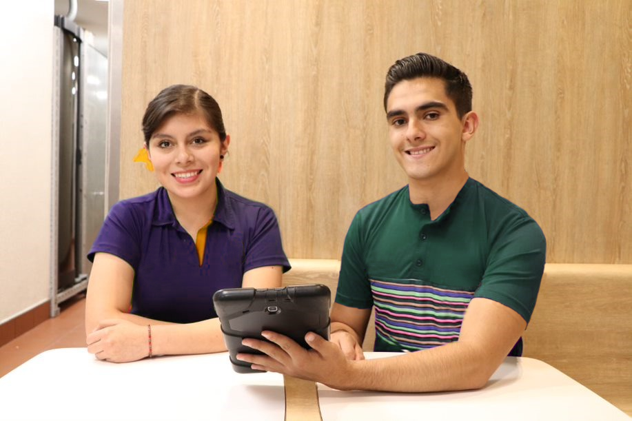 Two people doing training on a tablet