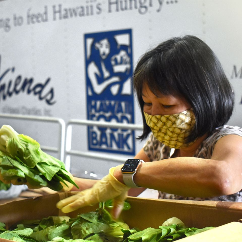 A volunteer sorts vegetables at a Feeding America-affiliated food bank in Hawaii
