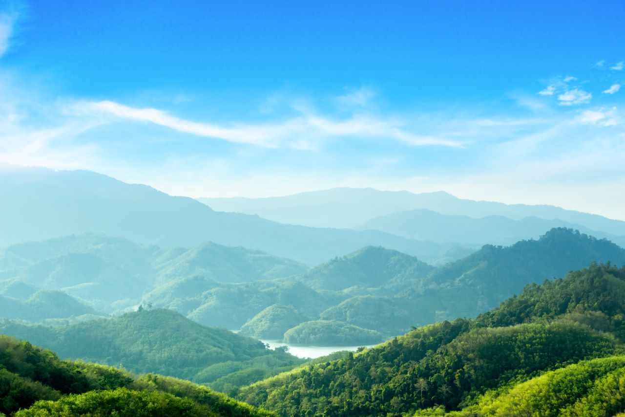 landscape with green mountains, river, and bright blue sky