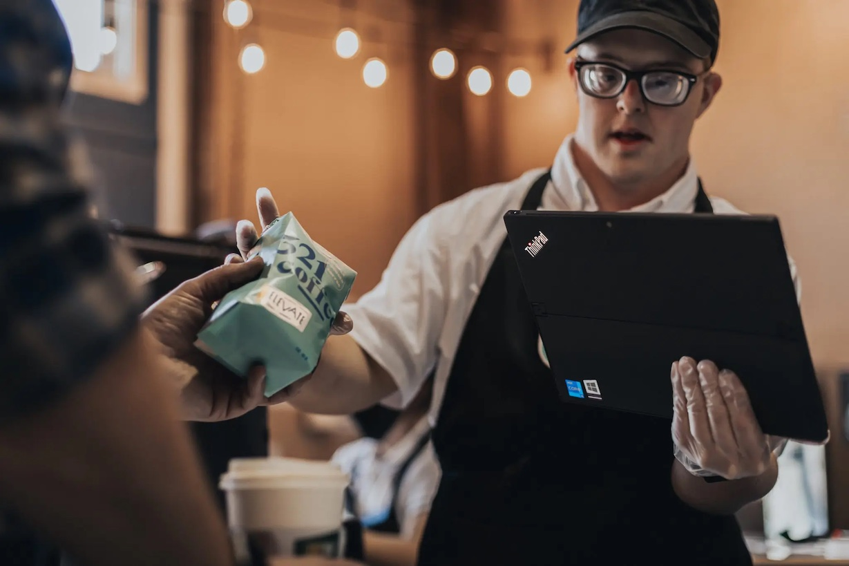 Coffee shop employee selling coffee through a tablet POS system