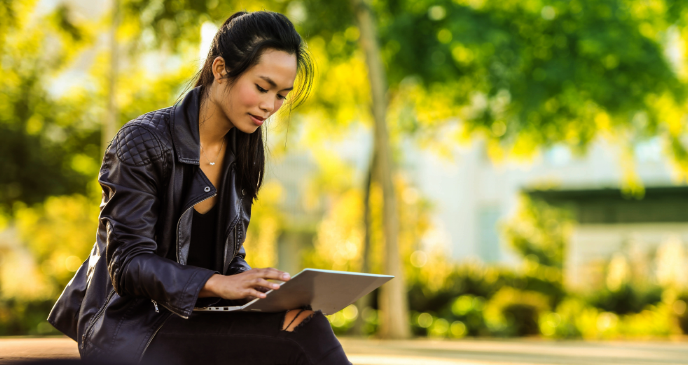 Image of a woman sitting on a park bench with her laptop