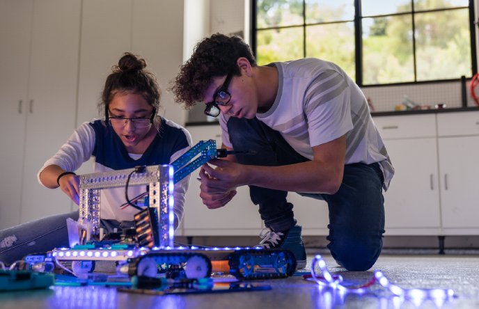 Image of two kids building a robot together