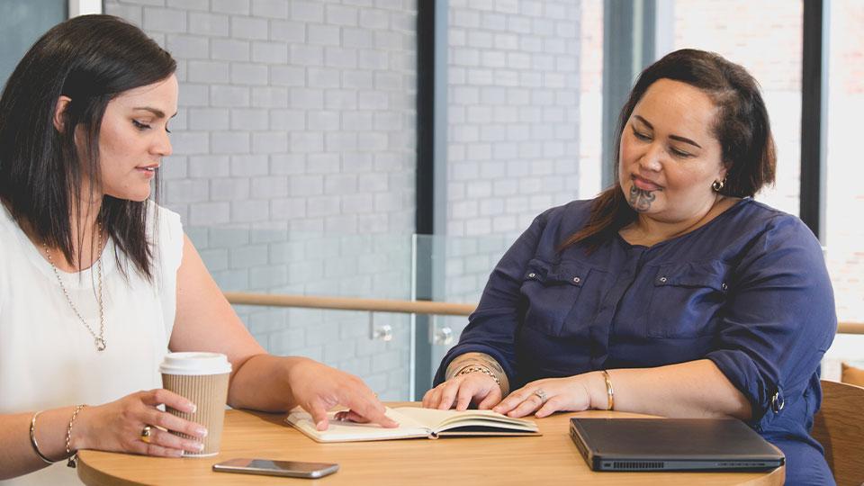 Two tetra tech employees reading a book