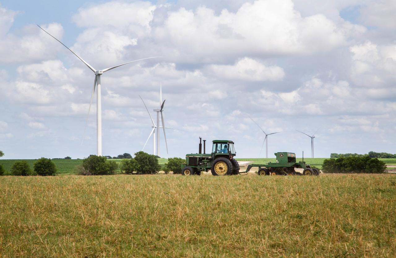 Tractor plowing a field below wind turbines