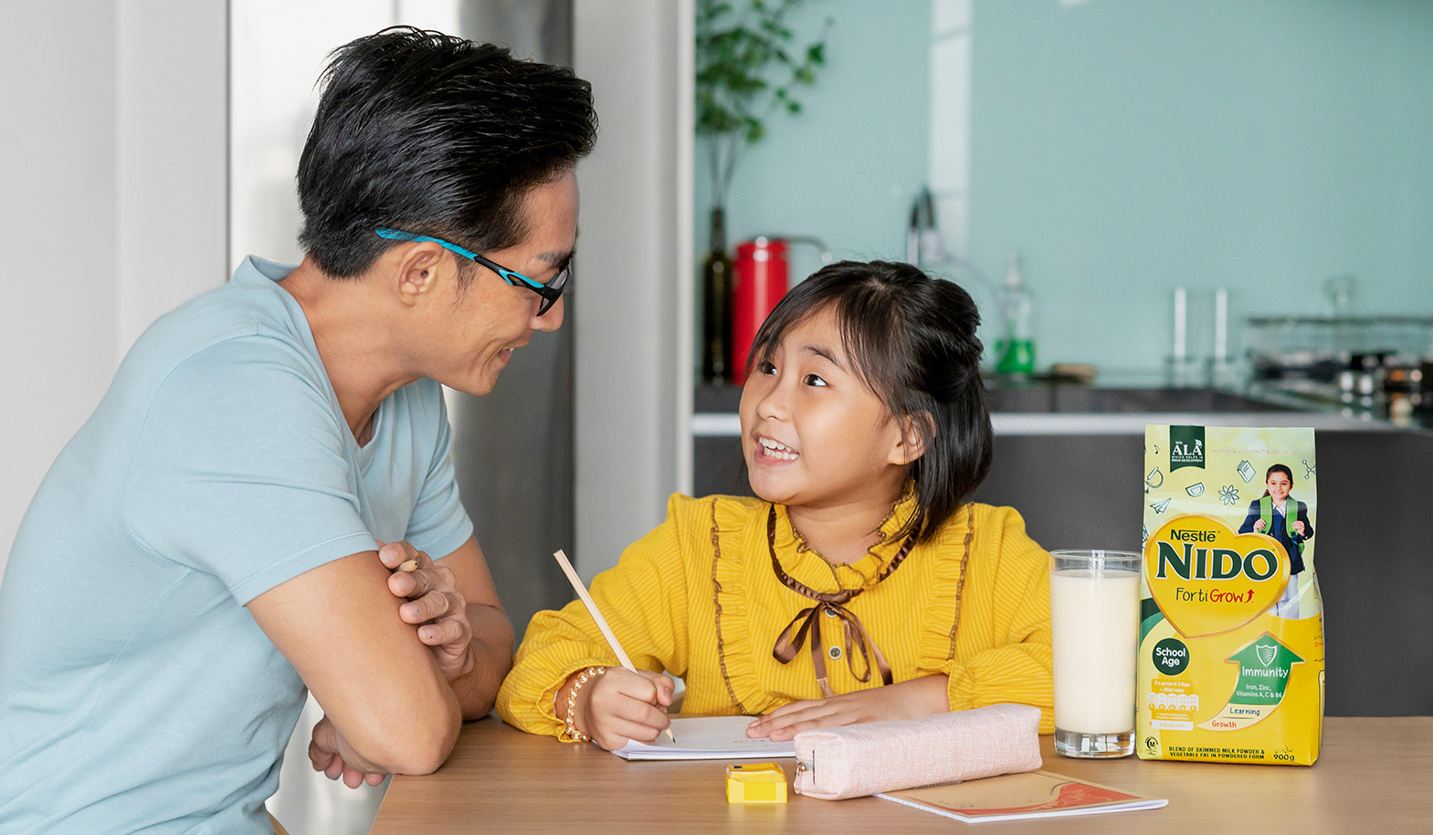 Father and daughter doing homework while drinking milk