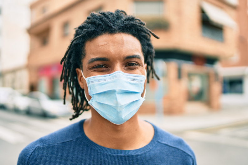 Person in blue shirt and blue face mask