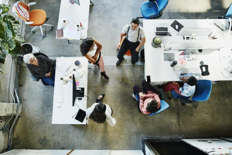 top down view of 6 employees working in an office