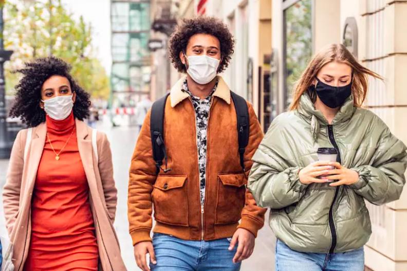 three masked people walking down the street