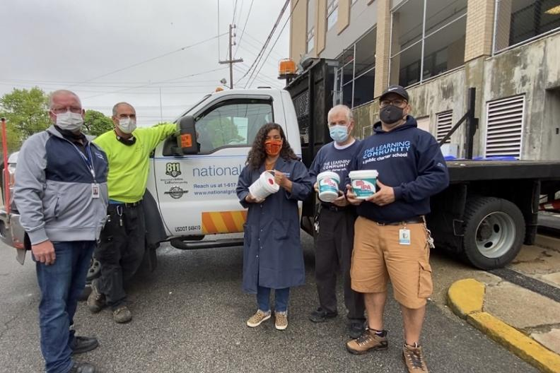 5 masked employees hold sanitizing wipes while standing in front of a truck.