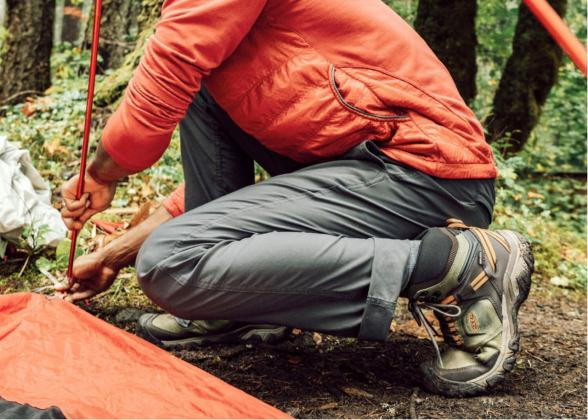 Person in orange jacket setting up a tent in the woods