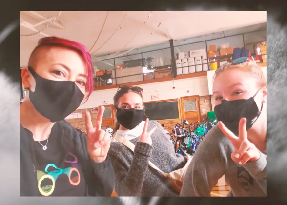 Three women wearing masks and holding up peace signs