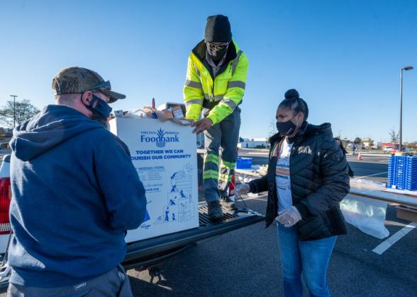 Three volunteers load donation into a truck