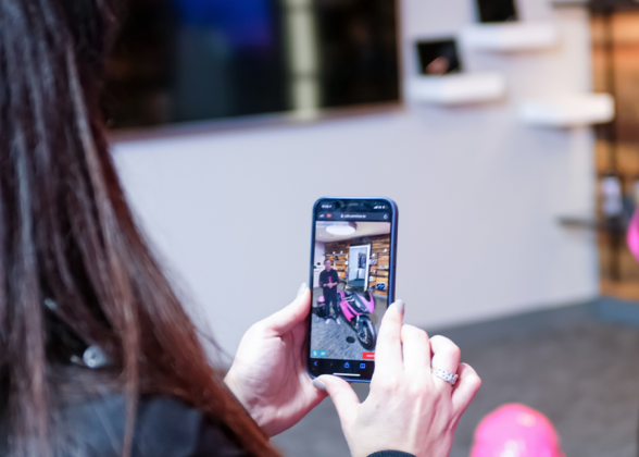 Woman holds her phone, looking at the hologram image on the screen