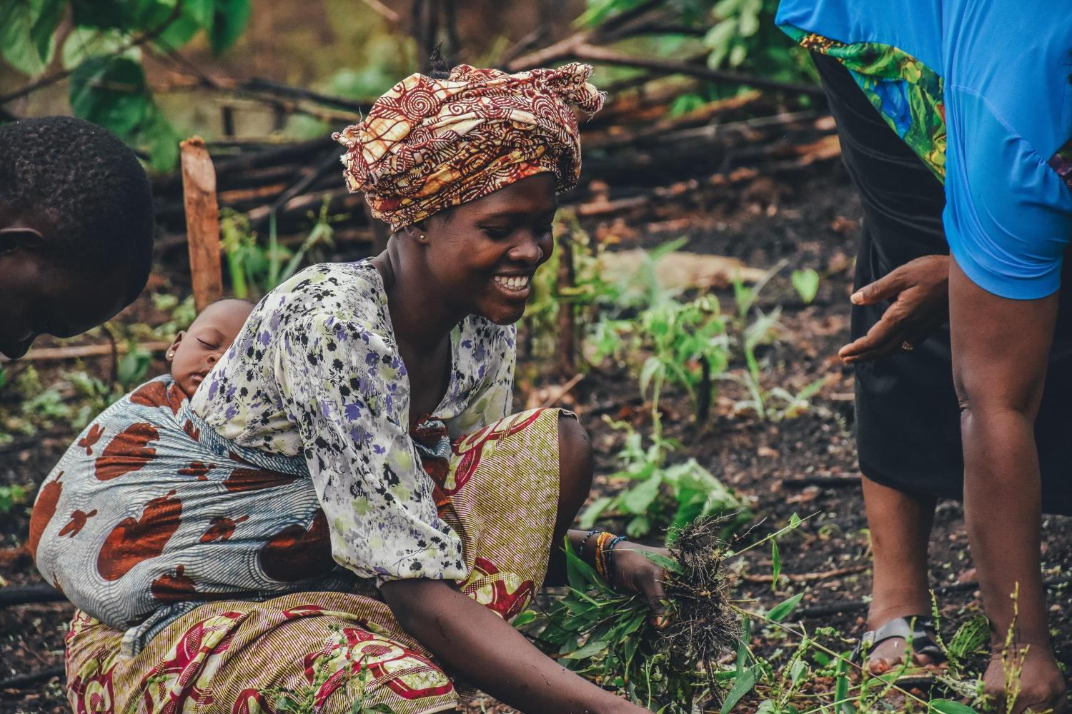 sustainable food systems - woman holding her baby while farming