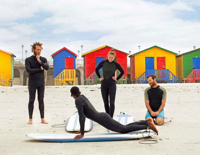 """Travelers participate in a """"Surf With Purpose"""" Social Impact Experience in Cape Town. Each lesson provides one month of surf therapy for a local child."""